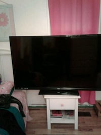 flat screen TV and white wooden TV stand 57 km