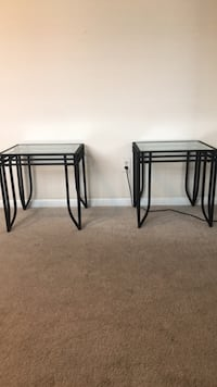 two black metal framed glass top tables