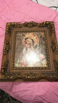 woman with pink and white headdress painting with brass-colored ornate frame