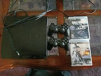 black Sony PS3 console with controllers and game c