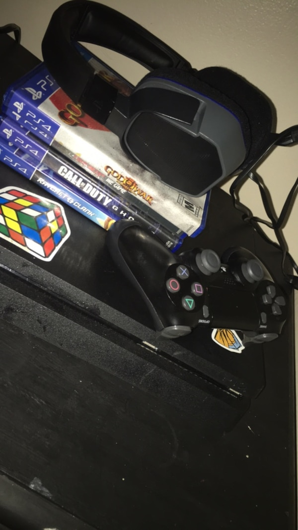 Black sony ps4 console with a controller and a headset with 4 games (negotiable)