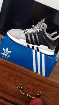 pair of white-and-black EQT support shoes with box
