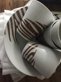four white ceramic cups and one white ceramic plate