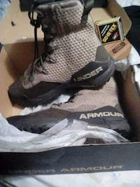 pair of brown Under Armour shoes with box
