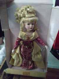 female doll with yellow and red dress and box