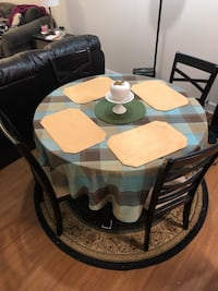 Larger circle breakfast table includes black wooden chairs with question, includes floor rug decorative, includes ceramic centerpiece and play mats, and also table cover. Gaithersburg, 20879