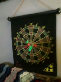 black and green dartboard with dart pins 3737 km