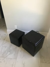 two square black leather ottomans