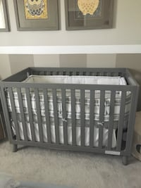 Baby's gray wooden crib and comfortable mattress