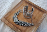silver-colored cuff bracelet with necklace
