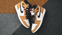 Pair of white-and-orange nike basketball shoes 538 km