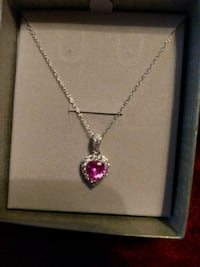 silver-colored necklace with pink gemstone pendant