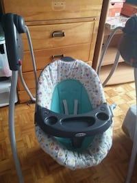 baby's white and green Graco swing chair