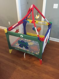baby's red, yellow, and green Graco travel cot