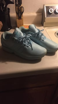 pair of blue Adidas lace-up low-top casual sneakers