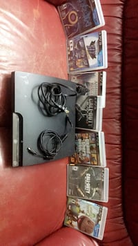 Black sony ps3 console with controller and 7 games