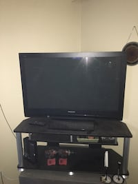 black flat screen TV with black wooden TV stand Surrey, V3S 4L2