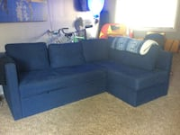 Blue fabric sectional sofa with pull out bed and storage compartment