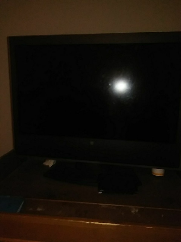 black 32 in flat screen TV with brown wooden stand