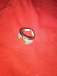 silver-colored ring with orange gemstone