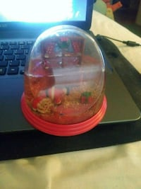Santa Claus snow globe with a present