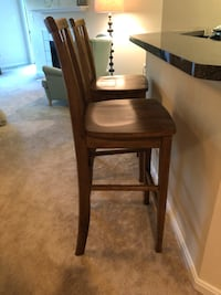 """2 solid wood honey brown bar stools similar to pottery barn Wynn Chairs! These are the real deal. Dimensions are 46"""" tall, 30"""" to seat, actual seat is 18w x 16. These are amazing. I would keep them forever however moving to a modern home. Slight blemishes Reston, 20194"""