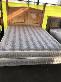 brown wooden bed with gray floral mattress
