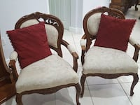 two white floral padded brown wooden armchairs and two red throw pillows Miami, 33187