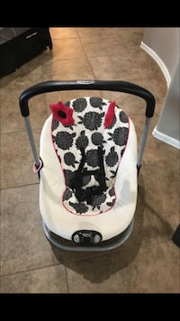white, black, and red floral bouncer