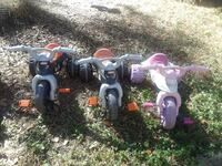 three assorted ride on toy trikes
