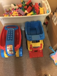 two plastic riding toy cars and interlocking toy block lot