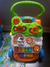 baby's green and white Vtech learning walker