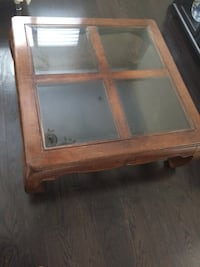 Square brown wood-framed glass coffee table