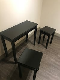 rectangular black wooden table and two stools