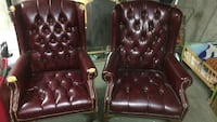 two tufted brown leather-padded Chesterfield sofa chairs