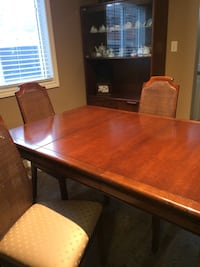 Rectangular brown wooden table with chairs and china hutch