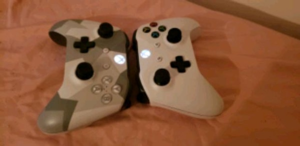 two white and black Xbox One controllers