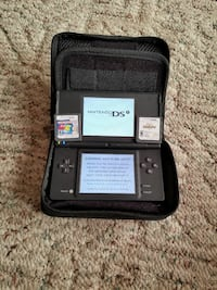 Nintendo DSi with two game cartridges an case