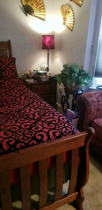 brown wooden bed frame with red and white floral bedspread Upper Marlboro, 20772