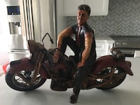Vintage motorcycle.  Man sitting on his motorcycle. Vintage statue made of wood, tires are of rubber. Mississauga, L4Z 3Y9