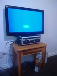 black flat screen TV with brown wooden TV stand Edmonton, T6E 2C2