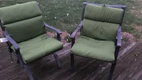 two gray steel framed green padded armchairs