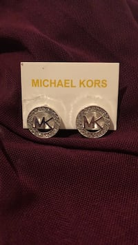 round silver-colored and diamond encrusted Michael Kors stud earrings