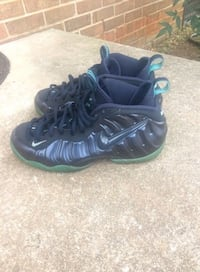 pair of black-and-green Nike Foamposite basketball shoes