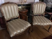 Two brown wooden with gray-and-beige striped pad armchairs.