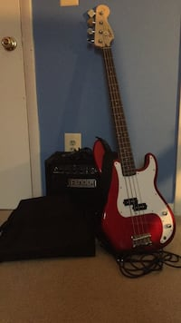 Red and white electric Bass with amplifier