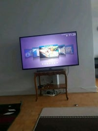 flat screen TV and brown wooden TV stand Toronto, M4E
