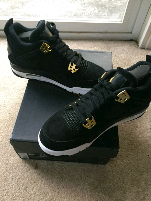 pair of black Air Jordan 4s with box