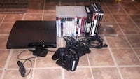 black Sony PS2 console with controllers and game cases Laval, H7K 2H4