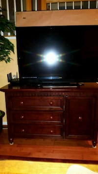 flat screen television with brown wooden TV stand Ashburn